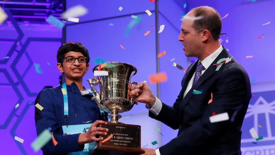 Karthik Nemmani, 14, from McKinney, Texas, holds the Scripps National Spelling Bee Championship Trophy with Scripps President and Chief Executive Officer Adam Symson after winning the Scripps National Spelling Bee in Oxon Hill, Md., May 31, 2018.