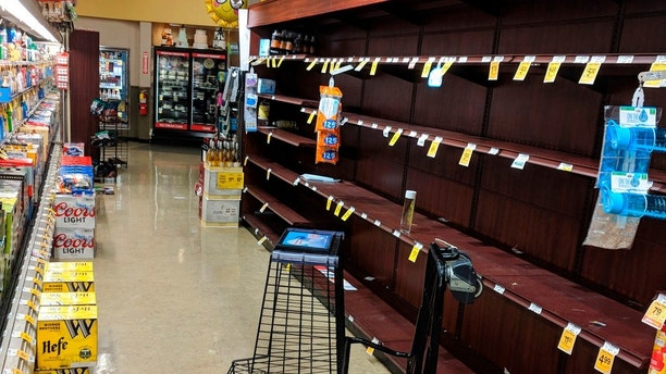 "Supermarket shelves are stripped bare of bottled water in Salem, Ore., late Tuesday May 29, 2018, after officials warned residents that tap water was unsafe for children and the elderly due to an algae bloom. The head of Oregon's emergency management agency has apologized after a cryptic emergency alert was forced out to cellphones in and around Oregon's capital city, displaying the words ""Civil Emergency"" and ""Prepare for Action,"" but carrying little other information. (AP Photo/Tom James)"