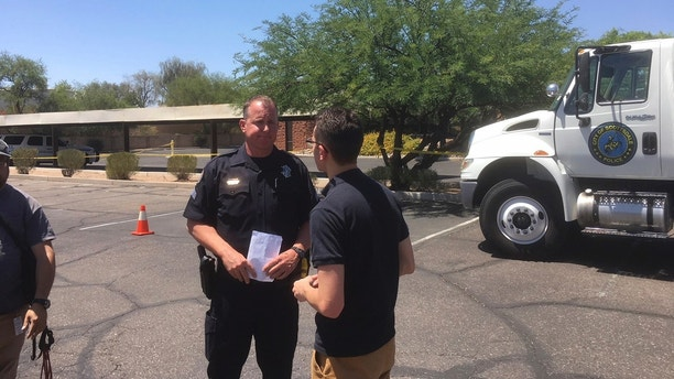 Scottsdale Police Sgt. Ben Hoster speaks to a member of the news media at the scene of a fatal shooting in Scottsdale, Ariz., on Saturday, June 2, 2018. The shooting death on Thursday of Dr. Steven Pitt, a prominent forensic psychiatrist who assisted in high-profile murder cases including serial killings in Phoenix is connected to the slayings of two paralegals, said authorities, who were looking into a possible fourth homicide Saturday. (AP Photo/Paul Davenport)
