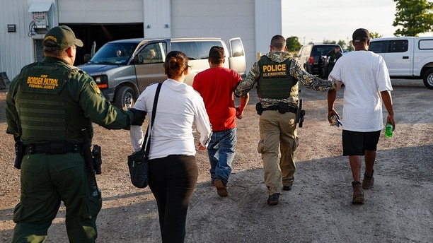 Government agents take suspects into custody during an immigration sting at Corso's Flower and Garden Center, Tuesday, June 5, 2018, in Castalia, Ohio. The operation is one of the largest against employers in recent years on allegations of violating immigration laws. (AP Photo/John Minchillo)