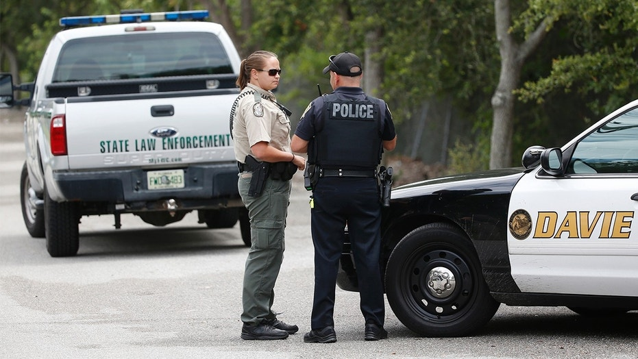 Law enforcement officers gather at the entrance of Silver Lakes Rotary Nature Park on Friday in Davie, Fla.
