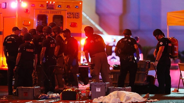 A body is covered with a sheet after a mass shooting in which dozens were killed at a music festival on the Las Vegas Strip on Sunday, Oct. 1, 2017. (Steve Marcus/Las Vegas Sun via AP)