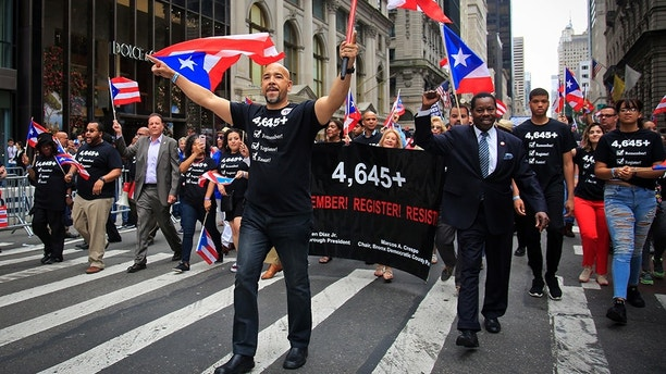 """Bronx Borough President Ruben Diaz, center, leads a group of state and city officials during the Puerto Rican Day Parade on Sunday, June 10, 2018, in New York. Their shirts and banner with """"4,645"""" represents the under-reporting of the death toll after after Hurricane Maria in Puerto Rico and a tepid emergency response by the administration of President Donald Trump. (AP Photo/Bebeto Matthews)"""