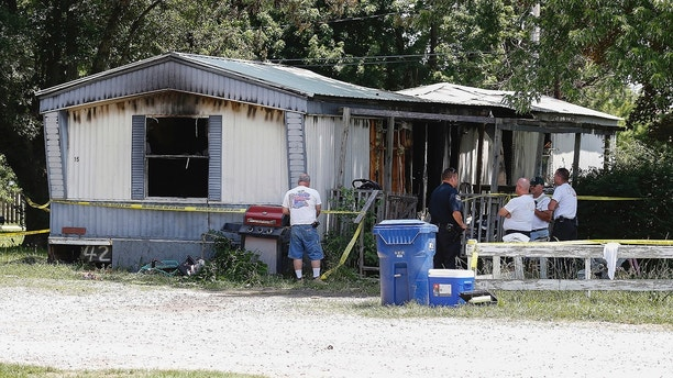 Investigators look over the remains of a deadly fire, Wednesday, June 6, 2018,  in Lebanon, Mo. Authorities say five children were killed and a woman injured in the mobile home fire in southern Missouri. (Nathan Papes/The Springfield News-Leader via AP)