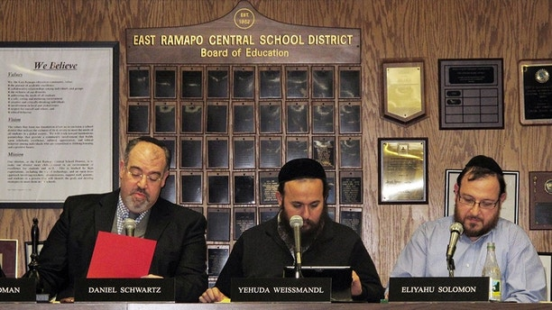From left, East Ramapo School Board President Daniel Schwartz and board members Yehuda Weissmandl and Eliyahu Solomon attend a board meeting on Tuesday, March 19, 2013, in Spring Valley, N.Y. Allegations of racism and anti-Semitism are afflicting the district, where the board is dominated by ultra-Orthodox Jews and the public school children are mostly black and Hispanic. (AP Photo/Jim Fitzgerald)