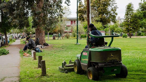 A UC Berkeley grounds keeper mows the lawn at People's Park in Berkeley, Calif. on April 18, 2018.