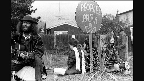BERKELEY, CA - 1970: A man plays a guitar as others surround a sign that says People's Park circa 1970 in Berkeley, California. (Photo by Robert Altman/Michael Ochs Archives/Getty Images)