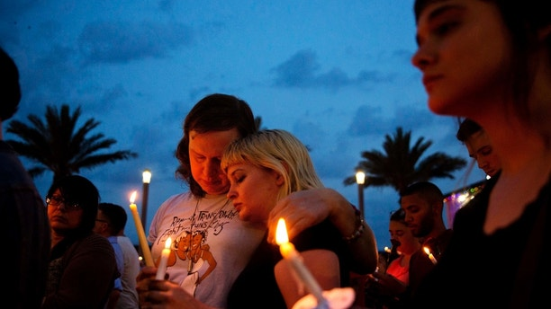FILE - In this June 13, 2016, file photo, Lucinda Rex, right, and Clarity Thorne embrace during a candlelight vigil downtown for the victims of a mass shooting at the Pulse nightclub in Orlando, Fla. Survivors and victims' relatives are marking the second anniversary of the Pulse nightclub shooting with a remembrance ceremony, a run, art exhibits and litigation. (AP Photo/David Goldman, File)