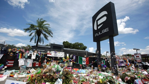 FILE - In this July 11, 2016, file photo, a makeshift memorial continues to grow outside the Pulse nightclub, the day before the one month anniversary of a mass shooting, in Orlando, Fla. Survivors and victims' relatives are marking the second anniversary of the Pulse nightclub shooting with a remembrance ceremony, a run, art exhibits and litigation. (AP Photo/John Raoux, File)