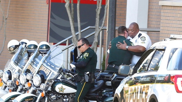 A Orange County Sheriff Motor deputy,center, gives support to a Orlando Police Motor officer,right, at Orlando Regional Medical Center after a OPD officer was shot and severely injured while responding over night to a domestic dispute call Monday, June 10, 2018. (Red Huber /Orlando Sentinel via AP)