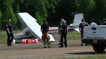 Ted Stevens Anchorage International Airport fire department and National Transportation Safety Board personnel respond to a damaged aircraft at Lake Hood Seaplane Base on Wednesday, June 13, 2018, in Anchorage, Alaska. Alaska State Troopers say two planes were involved in a mid-air collision Wednesday north of Anchorage, with the wreckage of one plane spotted in a river and the other landing at the seaplane base. (AP Photo/Mark Thiessen)