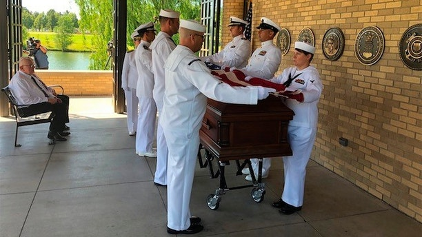 In this photo provided by the Ft. Logan National Cemetery Complex shows U.S. Navy pallbearers fold the flag for sailor Wallace Eakes, who was killed in the Japanese attack on Pearl Harbor, who was reburied with full military honors at Fort Logan National Cemetery in Denver, Colo., Thursday, June 21, 2018. Eakes' previously unknown remains were identified through DNA. About 100 people, mostly veterans with no other connection to Eakes besides their military service, attended the service. (Mat S. Williams/Ft. Logan National Cemetery Complex via AP)