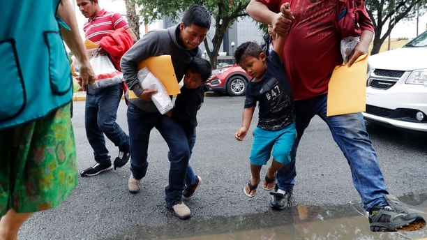 Young immigrants are lifted over a puddle as they arrive with their parents at the Catholic Charities RGV after they were processed and released by U.S. Customs and Border Protection, Tuesday, June 19, 2018, in McAllen, Texas. (AP Photo/Eric Gay)