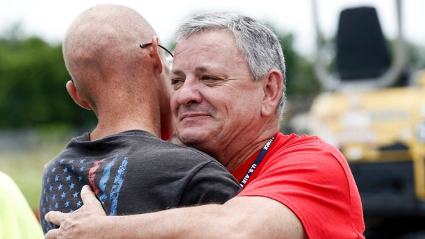 Tony Heineman, advancement and development officer for Soldier's Wish, hugs Cody Nichols, left, after presenting him with new lawn equipment at Bloss Equipment in Tulsa, Okla., on Friday, June 22, 2018.  Nichols, a veteran whose life and business were disrupted when his lawn equipment was stolen received $15,000 worth of new lawn-mowing equipment through the nonprofit group Soldier's Wish. The Tulsa-based organization works to meet the needs of military veterans.  (Morgan Hornsby /Tulsa World via AP)