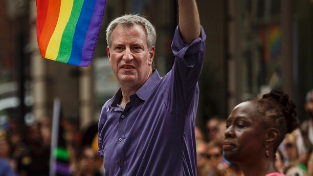 New York City Mayor Bill de Blasio waves acknowledges the crowd, along with his wife, Chirlane McCray, during the New York City Pride Parade, Sunday, June 24, 2018. (AP Photo/Andres Kudacki)