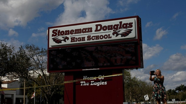 People take pictures in front of the Marjory Stoneman Douglas High School, following a mass shooting in Parkland, Florida, U.S., February 18, 2018. REUTERS/Carlos Garcia Rawlins - RC1104664FB0