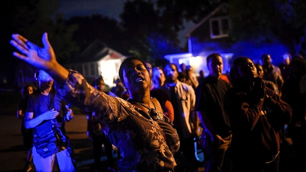 Minneapolis NAACP President Leslie Badue called for the attention of the crowd gathered at North 48th Avenue and Camden Avenue North before leading a prayer in response to an officer-involved shooting which took place hours earlier Saturday, June 23, 2018 in Minneapolis. Police in Minneapolis say officers shot and killed a man who was firing a handgun as he walked down a city street. (Aaron Lavinsky/Star Tribune via AP)