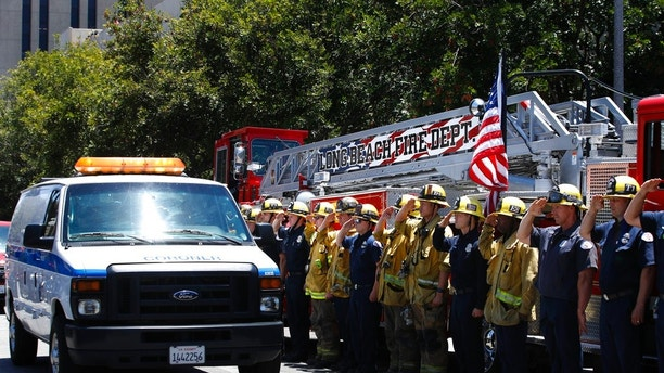 Firefighters salute as a van carrying the body of Long Beach Fire Capt. Dave Rosa passes them during a procession Monday, June 25, 2018, in Long Beach, Calif. Rosa was killed Monday morning after a resident of a retirement home opened fire on firefighters responding to a report of an explosion. (AP Photo/Jae C. Hong)
