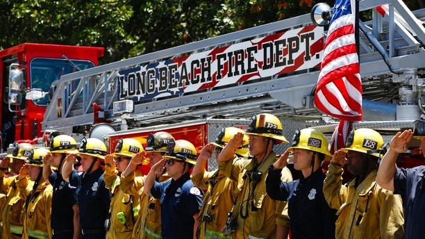 Firefighters salute during a procession for Fire Capt. Dave Rosa who was killed after he was shot responding to an emergency at a senior home in Long Beach, Calif., on Monday, June 25, 2018. A resident of a retirement home in Southern California opened fire on firefighters responding to a report of an explosion in the building, killing Rosa, and wounding others. (AP Photo/Jae C. Hong)