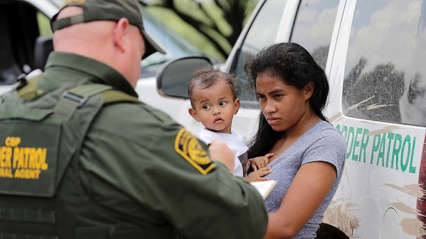A mother migrating from Honduras holds her 1-year-old child as surrendering to U.S. Border Patrol agents after illegally crossing the border Monday, June 25, 2018, near McAllen, Texas. (AP Photo/David J. Phillip)