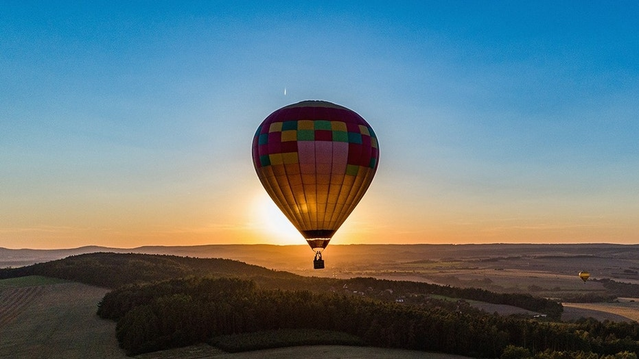 Hot air balloon in flight in the backlight of the setting sun.