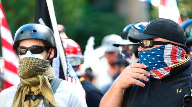 People demonstrate in a march by Patriot Prayer in Portland, Ore., on Saturday, June 30, 2018. Police dispersed clashing protesters as problems occurred when two opposing protest groups — Patriot Prayer and antifa — took to the streets. (Mark Graves/The Oregonian via AP)