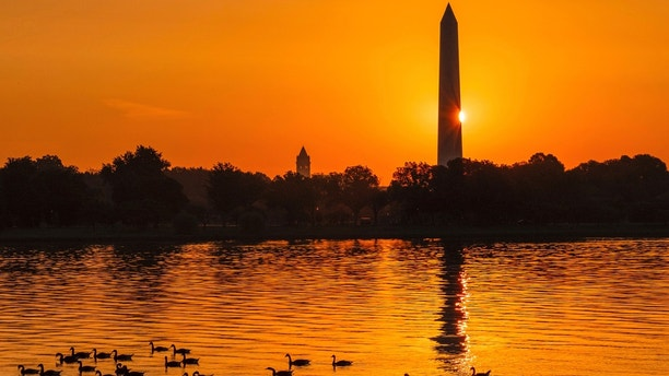 The sun peaks around the Washington Monument as geese float down the Potomac River at daybreak Sunday, July 1, 2018, in Washington on what is expected to be another hot day in the Nation's Capital. (AP Photo/J. David Ake)