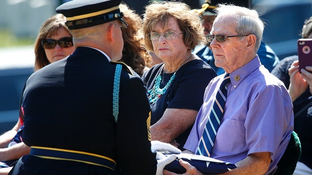 Wayne Brazeau, right, next to his wife Dorothy Brazeau, is handed the flag by 1st Sgt. Raymond Wrensch, left, during the burial service at Arlington National Cemetery, Tuesday, July 10, 2018, in Arlington, Va., for Army Air Force Staff Sgt. John H. Canty, of Winsted, Conn., whose plane was shot down over France during World War II. Canty was only 22 when he was declared missing in action in June 1944. Wayne Brazeau is the nephew of Canty.  (AP Photo/Jacquelyn Martin)