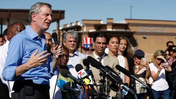 FILE - In this Thursday, June 21, 2018, file photo, New York Mayor Bill de Blasio speaks alongside a group of other U.S. mayors during a news conference outside a holding facility for immigrant children in Tornillo, Texas, near the Mexico border. U.S. Customs and Border Protection is alleging that de Blasio illegally crossed from Mexico into the U.S. while visiting the El Paso, Texas, area in June, an accusation the mayor's office flatly denies. (AP Photo/Andres Leighton, File)