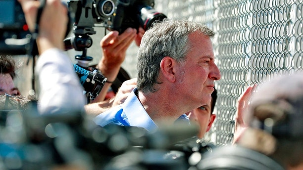 FILE - In this Thursday, June 21, 2018, file photo, New York City Mayor Bill de Blasio looks through a closed gate at the Port of Entry facility, in Fabens, Texas, where tent shelters are being used to house separated family members. U.S. Customs and Border Protection is alleging that de Blasio illegally crossed from Mexico into the U.S. while visiting the El Paso, Texas, area in June, an accusation the mayor's office flatly denies. (AP Photo/Matt York, File)