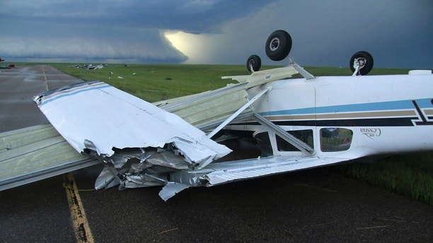 This Monday, July 9, 2018, evening photo provided by Brooks Photography shows a 175 Cessna plane upside down at the airport in Plentywood, Mont. Photographer Taylor Ordahl told KULR-TV that the first storm lasted for about 15 minutes and a second one lasted about 45 minutes and dropped ping pong ball-sized hail. A National Weather Service team was visiting northeastern Montana Tuesday to assess the damage after back-to-back thunderstorms uprooted trees, downed power lines, damaged buildings and flipped small airplanes at the airport in Plentywood. Officials say no injuries have been reported. (Taylor Ordahl/Brooks Photography via AP)