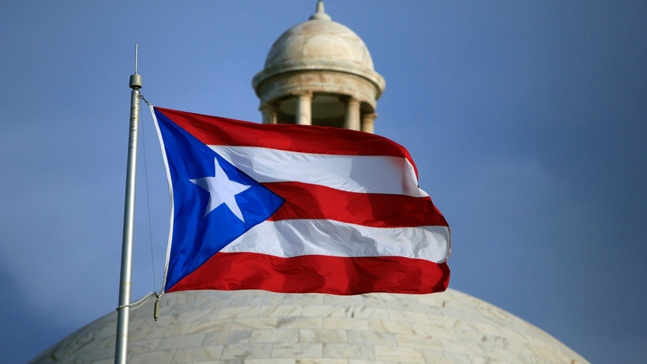 The flag of Puerto Rico flies outside the island's Capitol building in San Juan, July 29, 2015.
