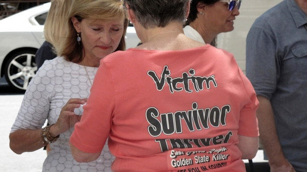 Jane Carson-Sandler, of South Carolina, who was raped by the so-called Golden State Killer in 1976, wears a t-shirt with a message to her attacker in Sacramento, Calif., Thursday, July 12, 2018, outside the Sacramento County jail after she and other victims and survivors attended a brief court hearing and saw the accused attacker, Joseph DeAngelo, for the first time. (AP Photo/Don Thompson)