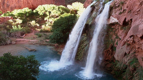 FILE - This 1997 file photo shows one of five waterfalls on Havasu Creek as its waters tumble 210 feet on the Havasupai Tribe's reservation in a southeastern branch of the Grand Canyon near Supai, Ariz. About 200 tourists are being evacuated from a campground on tribal land near famous waterfalls deep in a gorge off the Grand Canyon. Officials with the Havasupai Tribe say their reservation was hit with two rounds of flooding Wednesday, July 11, 2018, and early Thursday. (AP Photo/Bob Daugherty, File)
