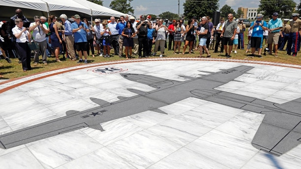 Family members, friends and military supporters and local residents look at the unveiled monument honoring the 15 Marines and a U.S. Navy corpsman who died in a 2017 plane crash near Itta Bena, Miss., during ceremonies Saturday, July 14, 2018. More than 200 relatives and friends of the 16 people who died aboard the flight with the call sign Yanky 72, joined a couple hundred county residents and military supporters at two ceremonies. (AP Photo/Rogelio V. Solis)