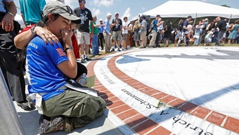 Morgan Zoufal, is comforted as she reacts to seeing the name of her late fiancee, Marine Sgt. Dietrich A. Schmieman, on a marble monument, honoring the 15 Marines and a U.S. Navy corpsman who died in a 2017 plane crash near Itta Bena, Miss., Saturday, July 14, 2018. More than 200 relatives and friends of the 16 people who died aboard the flight with the call sign Yanky 72, joined a couple hundred county residents and military supporters at two ceremonies, one on the campus of Mississippi Valley State University and the other across the street. (AP Photo/Rogelio V. Solis)