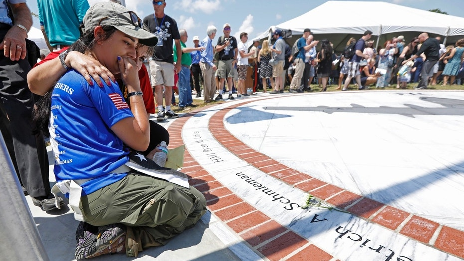 Morgan Zoufal, is comforted as she reacts to seeing the name of her late fiancee, Marine Sgt. Dietrich A. Schmieman, on a marble monument, honoring the 15 Marines and a U.S. Navy corpsman who died in a 2017 plane crash near Itta Bena, Miss., Saturday, July 14, 2018.