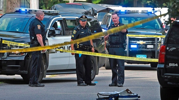 Officers work at the scene where a Weymouth police officer was shot and critically wounded while in a foot chase with a suspect following a vehicle crash on Sunday, July 15, 2018, in Weymouth, Mass. (Matt Stone/The Boston Herald via AP)
