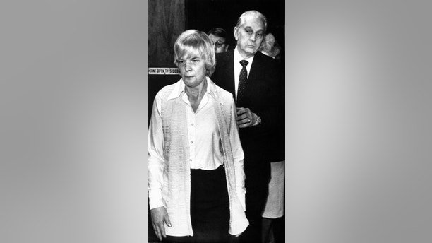 FILE - In this Feb. 1986 file photo, Marybeth Tinning is led from Schenectady County Court by Sheriff Bernard Waldron in Schenectady, N.Y. The New York state Department of Corrections and Community Supervision said Monday July 16, 2018 that Tinning, 75, has been granted parole and could be released from prison as early as next month. A jury convicted her of killing her ninth child, 4-month-old Tami Lynne, in December 1985. Eight of Tinning's children all died between 1972 and 1985 under suspicious circumstances. (AP Photo, File)
