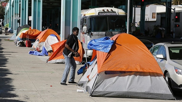 FILE - In this Feb. 23, 2016 file photo, a man stands outside his tent on Division Street in San Francisco. San Francisco voters will decide in November 2018 whether to tax large businesses to pay for homeless and housing services in a city struggling with income inequality. Supporters collected enough signatures to get the measure on the ballot. (AP Photo/Eric Risberg, File)