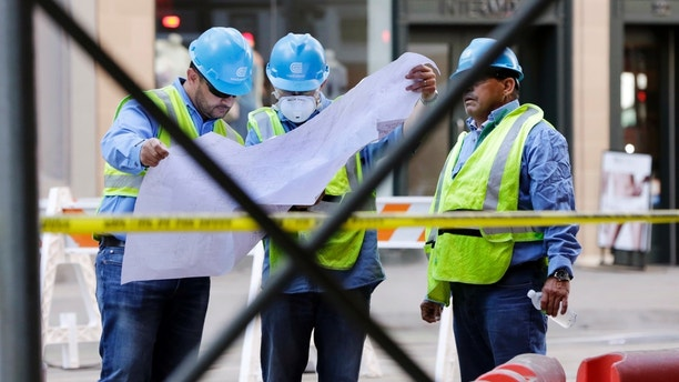 ConEd workers look at a map of pipes on New York's Fifth Avenue, Thursday, July 19, 2018. A steam pipe exploded beneath Fifth Avenue in Manhattan early Thursday, sending chunks of asphalt flying, a geyser of billowing white steam stories into the air and forcing pedestrians to take cover. (AP Photo/Richard Drew)
