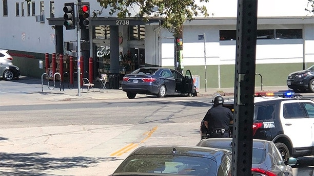 In this photo provided by Christian Dunlop, police officers stand guard near a crashed vehicle outside a Trader Joe's store in the Silver Lake neighborhood of Los Angeles on Saturday, July 21, 2018. Police believe a man involved in the standoff with officers shot his grandmother and girlfriend before firing at officers during a pursuit, then crashing outside the supermarket and running inside the store. (Christian Dunlop via AP)