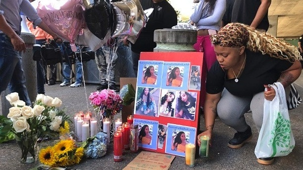 Malika Harris places a candle down for her sister Nia Wilson at a makeshift memorial outside the MacArthur Bay Area Rapid Transit station, Monday, July 23, 2018, in Oakland, Calif. A felon on parole fatally stabbed 18-year-old Nia Wilson in the neck and wounded her sister Lahtifa Wilson as they exited a train at a subway station in what police said was an unprovoked attack. BART Police Chief Carlos Rojas said officers are scouring the area for John Cowell, 27, who is suspected in the Sunday night attack at the MacArthur Station in Oakland. (AP Photo/Lorin Eleni Gill)