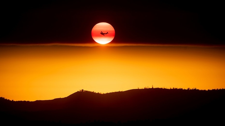 A plane battling the Ferguson Fire passes the setting sun over unincorporated Mariposa County, Calif., near Yosemite National Park. California authorities will shut down Yosemite Valley for several days as crews try to stop a stubborn and growing wildfire from spreading into Yosemite National Park. (AP Photo/Noah Berger, File)