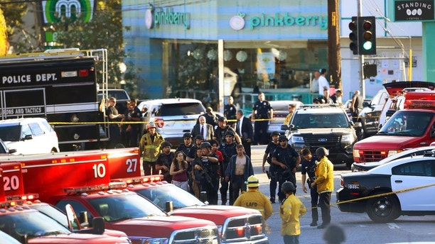 Los Angeles Police SWAT officers escort a group of Trader Joe's supermarket employees, after a gunman had barricaded himself inside the store in Los Angeles Saturday, July 21, 2018. Police believe a man involved in a standoff at the Los Angeles supermarket shot his grandmother and girlfriend and then fired at officers during a pursuit before he crashed into a utility pole outside the supermarket and ran inside the store. (AP Photo/Damian Dovarganes)