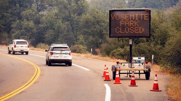 A sign on Highway 41 announces the closure of Yosemite National Park near Oakhurst, Calif., on Wednesday, July 25, 2018. Parts of the park closed Wednesday as firefighters work to contain the Ferguson fire burning nearby. (AP Photo/Noah Berger)