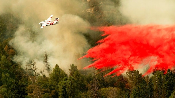 An air tanker drops retardant while fighting to stop the Ferguson Fire from reaching homes in the Darrah community of unincorporated Mariposa Count, Calif., Wednesday, July 25, 2018. (AP Photo/Noah Berger)