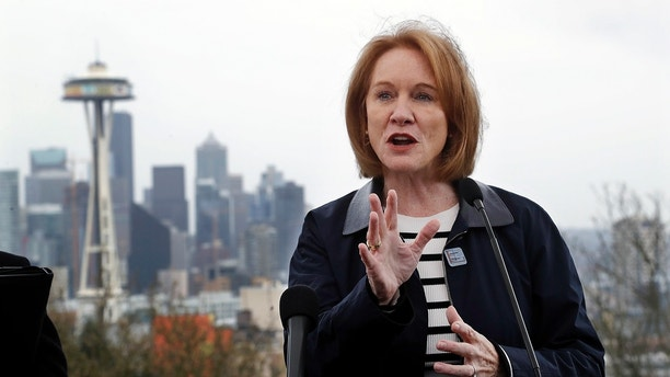 """Seattle Mayor Jenny Durkan speaks at a news conference talking about efforts to reduce greenhouse gases in the city as she stands at a viewpoint looking toward downtown Wednesday, April 4, 2018, in Seattle. Durkan wants to toll some downtown roads to try to ease the city's traffic gridlock. Such """"congestion pricing"""" is used in some European cities but so far no U.S. cit has established such a system. (AP Photo/Elaine Thompson)"""