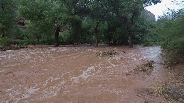 In this Wednesday, July 11, 2018 photo provided by Eric Kremer, torrents of water wash over a campground in Supai, Ariz. Hundreds of tourists who booked coveted overnight trips on tribal land deep in a gorge off the Grand Canyon will have to reschedule after heavy flooding forced evacuations and shut down the area for at least a week. (Eric Kremer via AP)