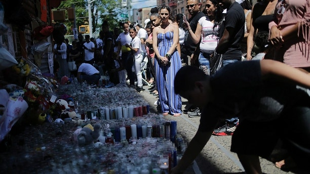 People leave candles and other mementos at a memorial to Lesandro Guzman-Feliz near the site of his murder in the Bronx borough of New York, Monday, June 25, 2018. Guerrero lives nearby and had gone to elementary school with the victim. Several suspects are in custody in New Jersey and awaiting extradition in connection with last week's killing of the 15-year-old boy in the Bronx that has sparked community outrage. Police said that Guzman-Feliz's death was gang related. The teen was attacked outside a bodega by a group of men and died after getting slashed in the neck with a machete. (AP Photo/Seth Wenig)